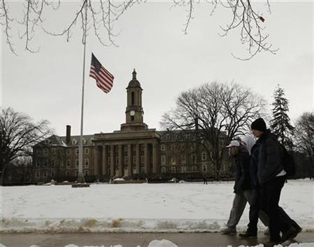 Students pass by a U.S. flag at half-staff at Penn State University's Old Main in State College, Pennsylvania, in honor of former head football coach Joe Paterno, January 23, 2012. REUTERS/Gary Cameron