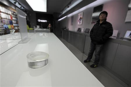 An employee stands next to an empty display desk which was used to put Apple iPads at a dealership in Hefei, Anhui province, February 15, 2012. A Chinese tech firm that claims it still owns the iPad trademark will seek a ban on exports of Apple Inc's computer tablets from China, which could deal a blow to the U.S. technology giant's sales worldwide. REUTERS/Stringer