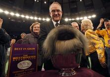 Handler David Fitzpatrick places Malachy, a Pekingese, into the silver bowl after he won Best In Show at the Westminster Kennel Club Dog Show in New York's Madison Square Garden February 14, 2012. REUTERS/Mike Segar