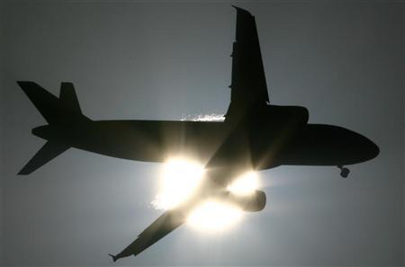 A passenger aircraft is silhouetted against the setting sun in New Delhi October 12, 2008. REUTERS/B Mathur/Files