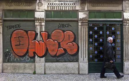 Man walk pasts a closed shop on Lisbon downtown February 14, 2012.   REUTERS/Jose Manuel Ribeiro