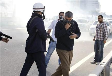 Riot police stop human rights Activist, Nabeel Rajab as he marches with other human rights activists towards Al Farook Junction, formally known as Pearl Square, on a highway leading to Manama, February 14, 2012. REUTERS/Hamad I Mohammed