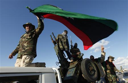 Members of the Libyan military force under the ruling of the National Transitional Council wave their national flag as they parade along a main street in Tripoli February 14, 2012. REUTERS/Ismail Zitouny