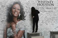 A Filipino fan writes a message on a tribute wall for the late American singer-actress Whitney Houston that is displayed inside a mall in Manila, February 15, 2012. 