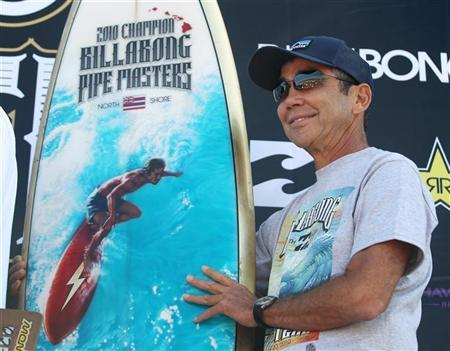 Legendary surfer Gerry ''Mr. Pipeline'' Lopez holds a retro-design trophy surfboard that he presented to 22-year-old Jeremy Flores of France who won the world's most prestigious and longest running professional surfing event: the Billabong Pipe Master at the Banzai Pipeline Haleiwa, Hawaii on December 16, 2010. REUTERS/Anthony Bolante