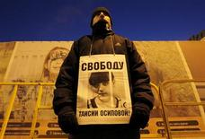 """Активист оппозиции с плакатом """"Свободу Таисии Осиповой"""" в ходе акции протеста на Триумфальной площади в Москве 31 января 2012 года. Смоленский областной суд в среду отменил приговор оппозиционной активистке Осиповой, осужденной на 10 лет за торговлю наркотиками. Осипова была включена в список политических заключенных, освобождение которых было одним из требований многотысячных акций протеста в столице. REUTERS/Anton Golubev"""