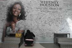 A Filipino fan writes a message on a tribute wall for the late American singer-actress Whitney Houston that is displayed inside a mall in Manila February 15, 2012. REUTERS/Romeo Ranoco
