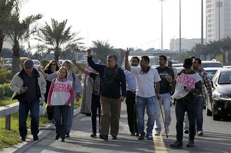 Human rights activist Nabeel Rajab (3rd L) shows a victory sign as he marches with other human rights activists towards Al Farook Junction, formally known as Pearl Square, on a highway leading to Manama, February 14, 2012. REUTERS/Hamad I Mohammed