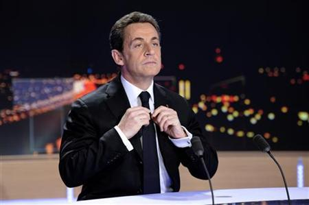 France's President Nicolas Sarkozy adjusts his tie prior to formally declaring his candidacy for a second term during the prime time news programme at the studios of TF1 French Television in Boulogne-Billancourt, near Paris, February 15, 2012. REUTERS/Lionel Bonaventure/Pool