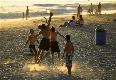 Boys play frisbee in the sand at Moonlight Beach in Encinitas, California June 30, 2011.   REUTERS/Mike Blake