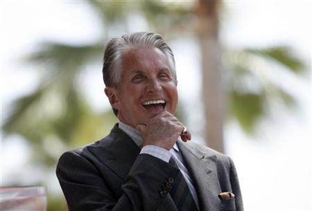 Actor George Hamilton laughs before accepting a star on the Walk of Fame in Hollywood, California August 12, 2009. REUTERS/Mario Anzuoni
