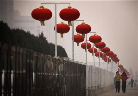 Pedestrians walk past Chinese lanterns that are part of celebrations for the upcoming lunar new year on a hazy day in Beijing January 18, 2012. REUTERS/David Gray