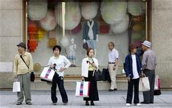 People wait for a bus to arrive in front of a shop window, where the lights have been turned off to conserve energy, at a department store in Tokyo May 19, 2011. REUTERS/Yuriko Nakao