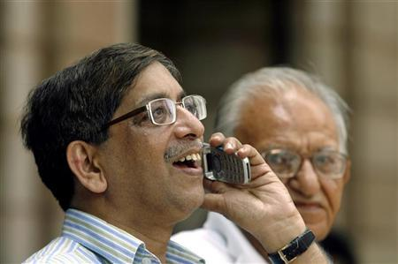 A man speaks on a phone as he looks at a large screen displaying India's benchmark share index on the facade of the Bombay Stock Exchange (BSE) building in Mumbai May 18, 2009. REUTERS/Punit Paranjpe/Files