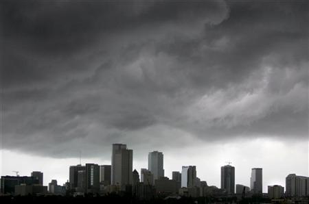 Dark clouds pass over the downtown of Miami, July 8, 2005. REUTERS/Carlos Barria