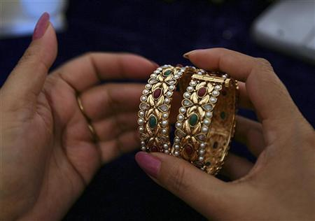 A customer selects one-carat gold bangles during an exhibition in Jammu April 13, 2008. REUTERS/Amit Gupta/Files