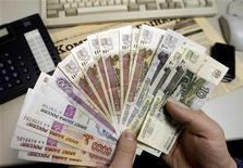 Человек держит в руках рублевые купюры в Санкт-Петербурге 18 декабря 2008 года. Рубль оставался в минусе вечером четверга, отражая неприятие риска на глобальных рынках, вызванное опасениями задержки второй программы финансовой помощи Греции и решением агентства Moody's поместить на пересмотр рейтинги 17 крупнейших мировых банков. REUTERS/Alexander Demianchuk