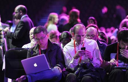 People attending the Nokia World event check their laptops and mobile devices in London October 26, 2011.  REUTERS/Paul Hackett
