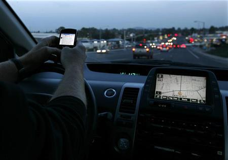 A driver uses his smart phone while in traffic in Encinitas, California December 10, 2009.   REUTERS/Mike Blake