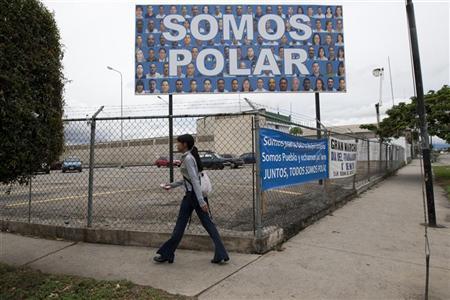 A women walks pass the food distribution plant of Polar in Barquisimeto May 27, 2010. REUTERS/Carlos Garcia Rawlins