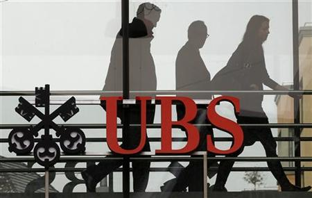People walk behind the logo of Swiss bank UBS in Zurich, February 7, 2012.  REUTERS/Arnd Wiegmann