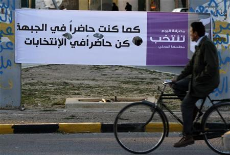 A resident cycles past a banner for upcoming local elections that reads, ''As you were present at the frontline, be there for the elections'', in Misrata February 14, 2012. REUTERS/Anis Mili