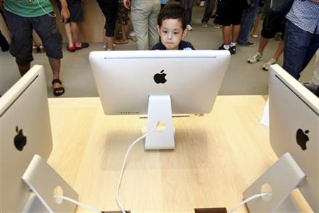 A boy looks at an Apple iMac desktop computer at the new Apple Store in Pudong Lujiazui, in Shanghai July 10, 2010. REUTERS/Aly Song