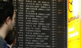 Люди смотрят на изменения в расписании рейсов в аэропорту во Франкфурте-на-Майне, 3 марта 2006 года. Забастовка небольшой группы работников франкфуртского аэропорта, третьего по величине в Европе, привела к отмене почти 300 рейсов. REUTERS/Alex Grimm