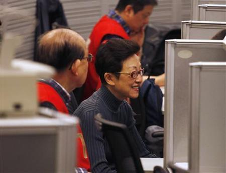 A floor trader smiles as she monitors share prices during morning trading at the Hong Kong Stock Exchange February 17, 2012. REUTERS/Bobby Yip