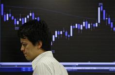 Трейдер проходит мимо информационного табло на бирже в Токио, 1 сентября 2009 года. Фондовые рынки Азии выросли в пятницу в надежде на долгожданное соглашение Греции с ЕС о повторной программе финансовой помощи и благодаря хорошей статистике США. REUTERS/Yuriko Nakao