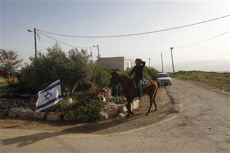 A Jewish settler rides his horse in the unauthorized Jewish outpost of Migron near the West Bank city of Ramallah  February 8, 2012. Migron perches high on a blustery hill in the occupied West Bank. Its inhabitants pay taxes, are hooked up to the electricity grid and get round-the-clock protection from Israeli soldiers. Over the past decade the government has spent at least 4 million shekels ($1.1 million) on establishing and maintaining the cluster of squat, prefab bungalows, even building a neat tarmac road up the steep incline to the treeless ridge. Yet despite all that state help, Migron is an illegal outpost, even under Israeli law, and its time is running out. Picture taken February 8, 2012. REUTERS/Baz Ratner (