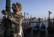 A masked reveller poses in Saint Mark's Square during the Venetian Carnival in Venice February 12, 2012. REUTERS/Manuel Silvestri