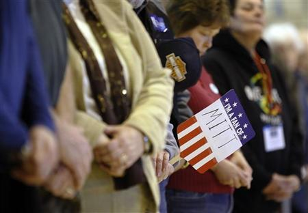 Voters bow their heads during the invocation at a Republican Caucus in Sanford, Maine February 11, 2012.   REUTERS/Brian Snyder