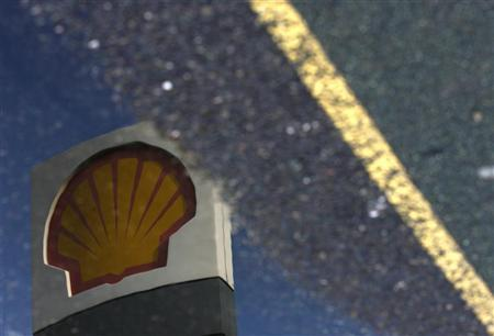 A Shell petrol station sign is reflected in a puddle in London April 28, 2009.  REUTERS/Luke MacGregor