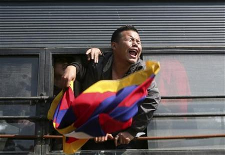 A Tibetan exile shouts slogans after being detained by police during a protest in front of the Chinese embassy in New Delhi February 16, 2012. REUTERS/Parivartan Sharma/Files