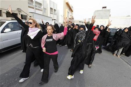 British activist Elaine (L) and U.S. activist Medea Benjamin (in pink) form victory signs with their fingers along with Bahraini anti-government protesters as they march to Al Farook Junction, formerly known as Pearl Square, in Budaiya, west of Manama February 17, 2012. REUTERS/Hamad I Mohammed