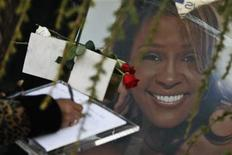 A woman writes a message at the entrance of Whigham Funeral Home, which is handling the funeral service of pop singer Whitney Houston, in Newark, New Jersey February 17, 2012. REUTERS/Eduardo Munoz