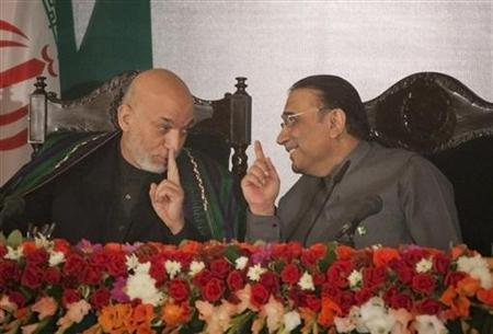 Afghanistan's President Hamid Karzai (L) and his counterpart from Pakistan, Asif Ali Zardari, chat during a joint news conference with Iran's President Mahmoud Ahmadinejad (unseen) in the President House in Islamabad February 17, 2012. REUTERS/Mian Khursheed