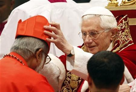 Pope Benedict XVI places a red biretta, a four-cornered hat, on the head of new Cardinal George Alencherry of India during a Consistory ceremony in Saint Peter's Basilica at the Vatican February 18, 2012. Pope Benedict XVI installed 22 new Roman Catholic cardinals from around the world on Saturday. REUTERS/Tony Gentile