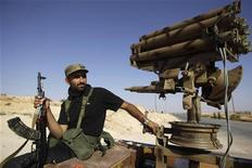 A Libyan rebel fighter sits next to a missile launcher in the back of a truck in Al-Qawalish, Libya July 14, 2011. REUTERS/Ammar Awad