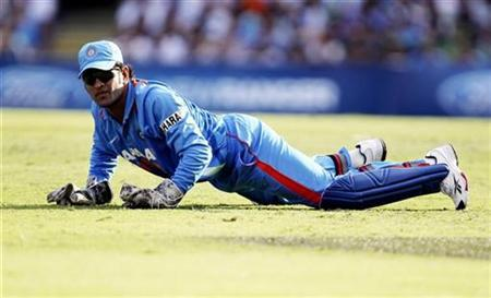 India's M.S Dhoni lies on the field during their one-day international cricket match against Australia in Brisbane February 19, 2012. REUTERS/Jason O'Brien
