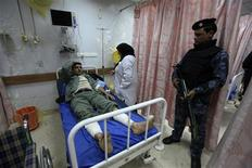 A police officer stands guard near his wounded comrade after a bomb attack, at a hospital in Baghdad February 19, 2012. REUTERS/Saad Shalash