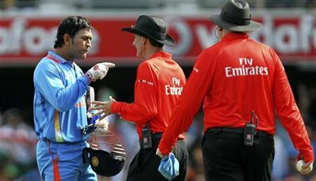 Mahendra Singh Dhoni (L) argues with umpire Billy Bowden after his appeal for the wicket of Mike Hussey was overturned and given not out during their one-day international cricket match in Brisbane February 19, 2012. REUTERS/Jason O'Brien