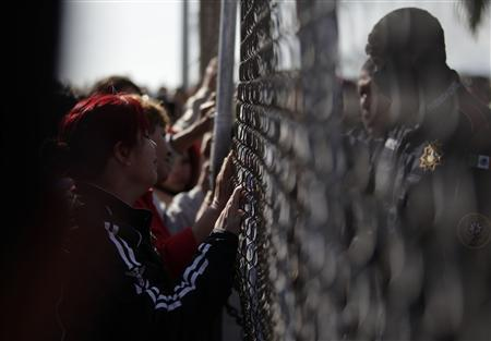 Relatives of inmates wait for news next to a fence as police officers stand guard inside the state prison in Apodaca, on the outskirts of Monterrey February 19, 2012. At least 20 people were killed after a fight broke out in the early hours of Sunday morning between guards and prisoners, who started a fire by setting mattresses alight, a government spokesman told Mexican television news. REUTERS/Daniel Becerril