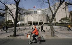 Мужчина проезжает мимо здания Центробанка Китая в Пекине, 16 февраля 2009 года. Центробанк Китая снизил норму банковского резервирования на 50 базисных пунктов в субботу ради замедления темпов сокращения роста второй по величине экономики мира. REUTERS/Jason Lee
