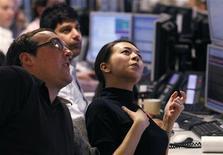 Трейдеры следят за биржевыми индексами в Лондоне, 24 марта 2010 года. Европейские рынки акций открылись ростом в понедельник благодаря решению Китая сократить нормы банковского резервирования, а также надеждам на то, что Греция наконец-то получит финансовую помощь. REUTERS/Andrew Winning