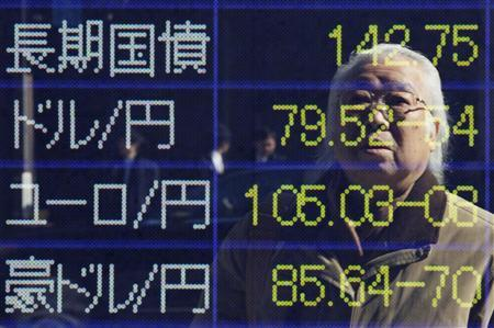 A man is reflected in an electronic board displaying foreign currency rates against the Japanese yen and the Japanese government bond outside a brokerage firm in Tokyo February 20, 2012. Japan's Nikkei share average climbed above its 1-year moving average on Monday after China eased policy to boost growth, while market players looked to a European meeting later in the day to seal a long-awaited Greek bailout. REUTERS/Yuriko Nakao