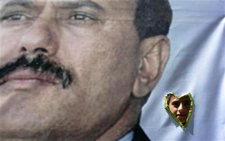 A boy looks through a hole in a banner, with an image of Yemen's outgoing President Ali Abdullah Saleh, as he performs the weekly Friday prayers during a rally to show support for him in Sanaa January 27, 2012. REUTERS/Mohamed al-Sayaghi