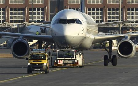 An airport apron controller vehicle is pictured in front of a Lufthansa Airbus A321-200 aircraft on the runway at Frankfurt airport February 20, 2012. REUTERS/Alex Domanski