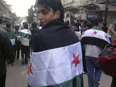 Demonstrators drape Syrian national flags over their backs during a protest against Syria's President Bashar al-Assad, in Kafranbel near Idlib February 19, 2012. REUTERS/Handout